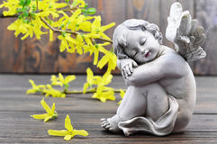 Angel guardian and spring flowers. On wooden background stock photo