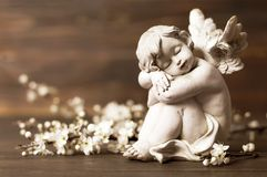 Angel guardian and spring flowers. On wooden background stock photos