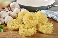 Angel hair pasta nests. Wiht mushrooms, onions and other spaghetti ingredients royalty free stock photography