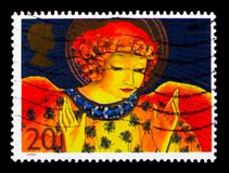 Angel with Hands raised in Blessings, Christmas, 1998, Angels serie, circa 1998. MOSCOW, RUSSIA - OCTOBER 3, 2017: A stamp printed in Great Britain shows Angel Royalty Free Stock Images