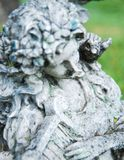 Angel With Harp. This is an old statue withered with time of an angel playing a harp Royalty Free Stock Images
