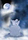 Angel headstone. An angel headstone sits under the moon in the heavens.  Marks a final peaceful resting space Royalty Free Stock Photography