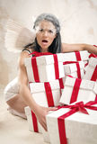 Angel with heap of gift boxes. Young woman as angel with heap of gift boxes Royalty Free Stock Images