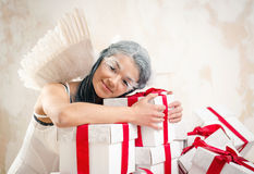 Angel with heap of gift boxes. Young woman as angel with heap of gift boxes Stock Photography