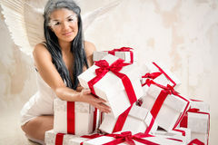 Angel with heap of gift boxes. Young woman as angel with heap of gift boxes Royalty Free Stock Photo