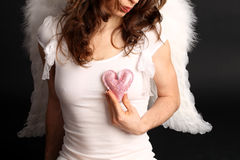 Angel heart. Woman with angel wings and heart on dark background stock photo