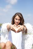 Angel with heart outdoors Stock Photo