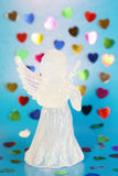 Angel with hearts. Glass angel on blue background with multicolor hearts Royalty Free Stock Photography