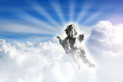 Angel in heaven. A Cute silver angel playing music instrument in the sky Stock Photos