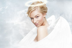 Angel in heaven. Young blond woman as beautiful angel witch wite wings and aureole stock photos