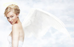 Angel in heaven. Young woman as angel with white wings in a clouds Royalty Free Stock Image