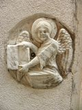 Angel holding a book carved into wall-Venice. A little traditional angel carved into a Venetian wall, holding a book, close up Stock Photo