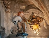 Angel holding a human skull and trumpet on a decoration in the Sedlec Ossuary, Kutna Hora, Czech Republic. Angel holding a human skull and trumpet on a royalty free stock photography