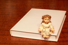 Angel and Holy Bible. Angel sitting on the edge of the book of the Holy Bible Royalty Free Stock Photo