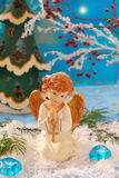 Angel kneeling on the snow and  praying. Christmas scene with angel figurine kneeling on the snow and praying Royalty Free Stock Images