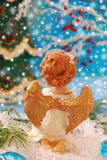 Angel kneeling on the snow and  praying. Christmas scene with angel figurine kneeling on the snow and praying Royalty Free Stock Image