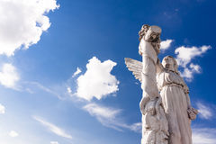 Angel in light. Old angel sculpture against bright blue sky and white clouds. Copy space Royalty Free Stock Images