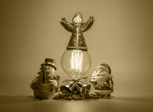 Angel on light bulb with Santa and Snow man. On gold color background Royalty Free Stock Photo