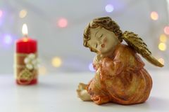 Angel with lit candle and bokeh lights on the background royalty free stock image