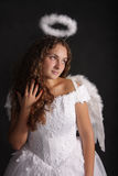 Angel looking left. Beautiful curly woman in white angel dress looking left Royalty Free Stock Photo