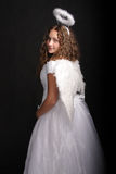 Angel looking over shoulder. Portrait of pretty girl in angel dress looking over shoulder Stock Photo