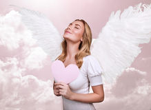 Angel of love. Cute girl with closed eyes in pink sky, cupid costume, fairy tale, fantasy dreaming, Valentine day, enjoying love relationship Royalty Free Stock Photo