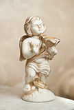 Angel with lyre, ornament. Golden ornament. Vintage angel. Ceramic angel playing harp. Cupid statuette on marble. Stock Image