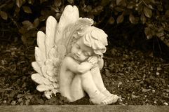 Angel made of clay sitting in a hedge on a grave royalty free stock image