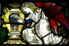 Angel making music (stained glass). A photo of an angel making music (stained glass royalty free stock photos