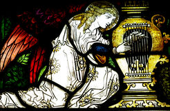 Angel making music (stained glass). A photo of an angel making music (stained glass stock image