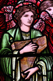 An angel with a music instrument in stained glass
