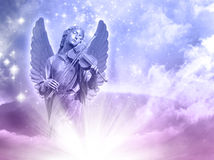 Angel of music. An angel statue over mystical sky with divine light and stars Royalty Free Stock Photo
