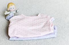 Baby clothes. An angel near a Baby clothes on a baby `s bed royalty free stock images