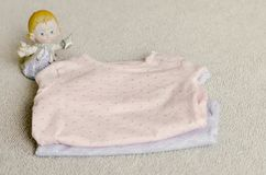 Baby clothes. An angel near a Baby clothes on a baby `s bed stock photo