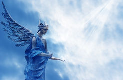 Angel over blue sky with rays of sun light Stock Photo