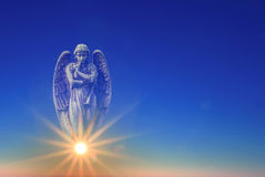 Angel over blue sky with rays of sun light with copy space Stock Images