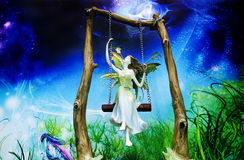 Angel in the paradise. Mystical angel shaking swing in the paradise Stock Photography
