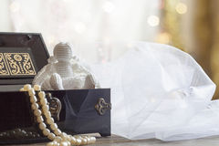 Angel and Pearls necklace in black casket on colorful background bokeh Stock Photos