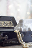 Angel and Pearls necklace in black casket on colorful background bokeh Stock Images