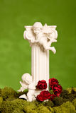 Angel pillar with moss on green background Royalty Free Stock Photos