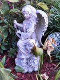 Angel playing harp in a garden Royalty Free Stock Photography