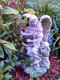 Angel playing harp in a garden Stock Photo