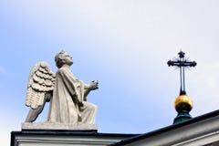 Angel praying. Praying Angel under the steel cross Royalty Free Stock Images