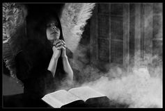 Angel praying. With close-up on the face and hands with bible out of focus black and white Royalty Free Stock Image