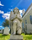 Angel praying in a cemetery royalty free stock photography