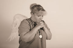 Angel praying nurse. A angelic nurse praying for help royalty free stock photos
