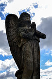 Angel praying. Statue of an angel looking at the blue sky and pray for the forgiveness of humanity Stock Photography