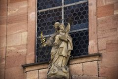 Angel and priest statue at front of classic retro building in He royalty free stock image