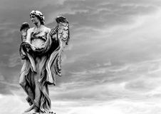Angel before the rain. Statue against rain clouds - black and white Stock Photo