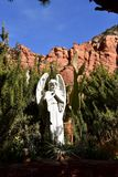 Angel by red rock mountains of Sedona and the Holy Cross chapel. Hidden in the bushes in front of the red rock mountains of Sedona is a white sculpture of an stock photos